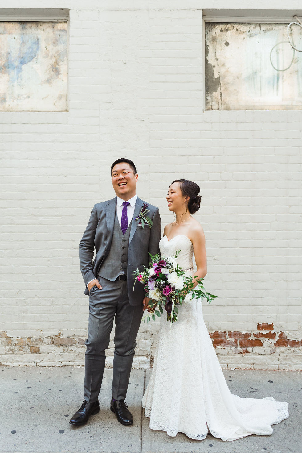 bride and groom standing hand in hand in front of white brick wall on their way to their Parisian inspired wedding at La Maquette in Toronto Ontario