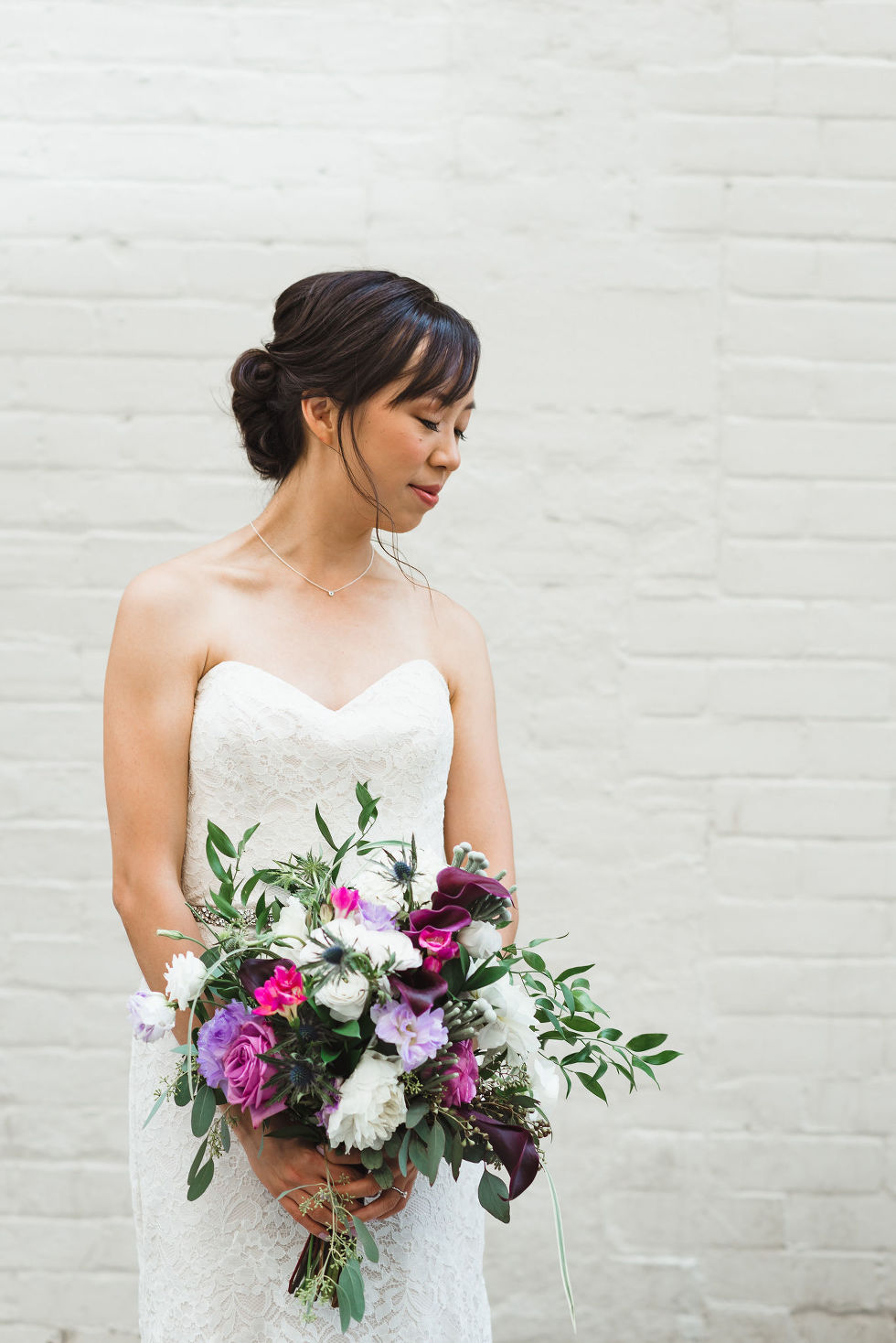 bride standing in front of white brick wall with purple and pink floral bouquet before her Parisian inspired wedding at La Maquette in Toronto Ontario