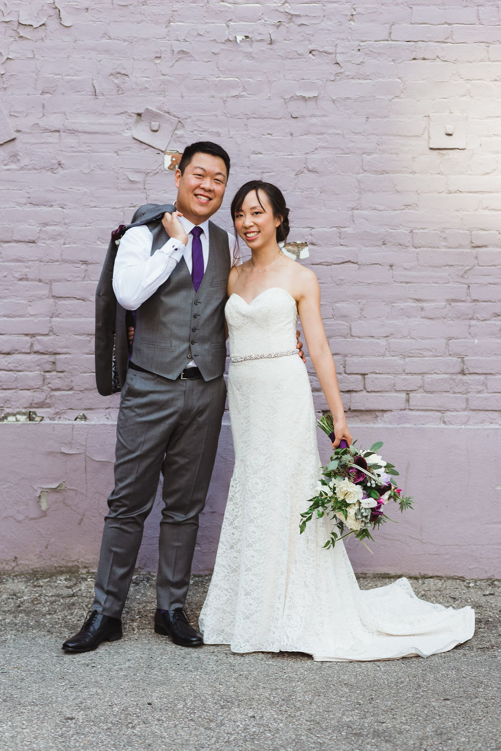 bride standing next to her groom as he puts his suit jacket over his shoulder in front of white brick wall on their way to their Parisian inspired wedding at La Maquette in Toronto Ontario