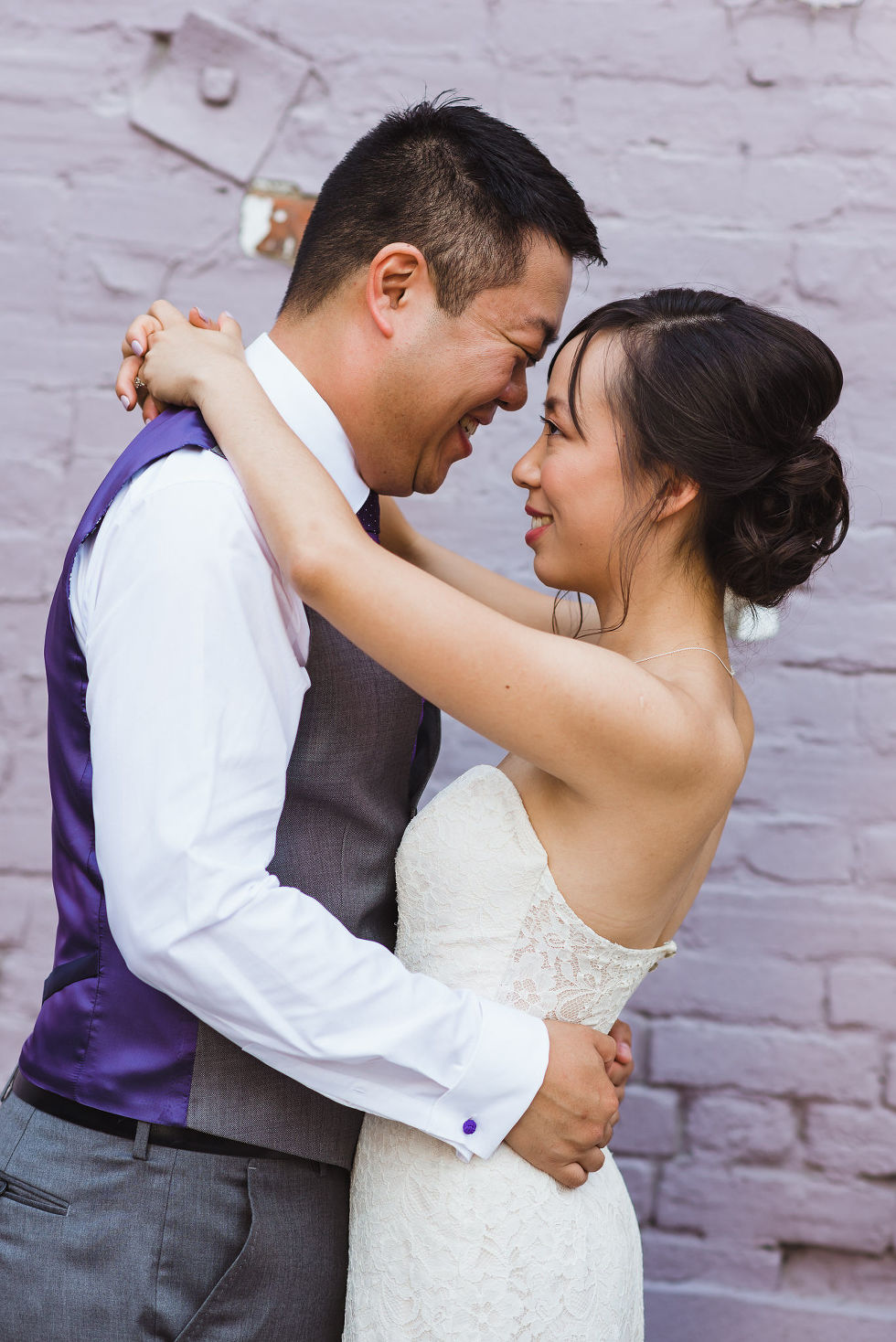 bride and groom in a loving embrace in front of white brick wall on their way to their Parisian inspired wedding at La Maquette in Toronto Ontario