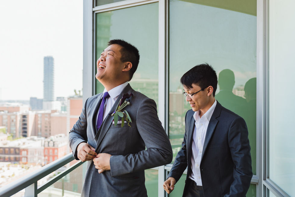 Groom laughing while he buttons up his suit in front of groomsman on a condo balcony before his Parisian inspired wedding at La Maquette in Toronto Ontario