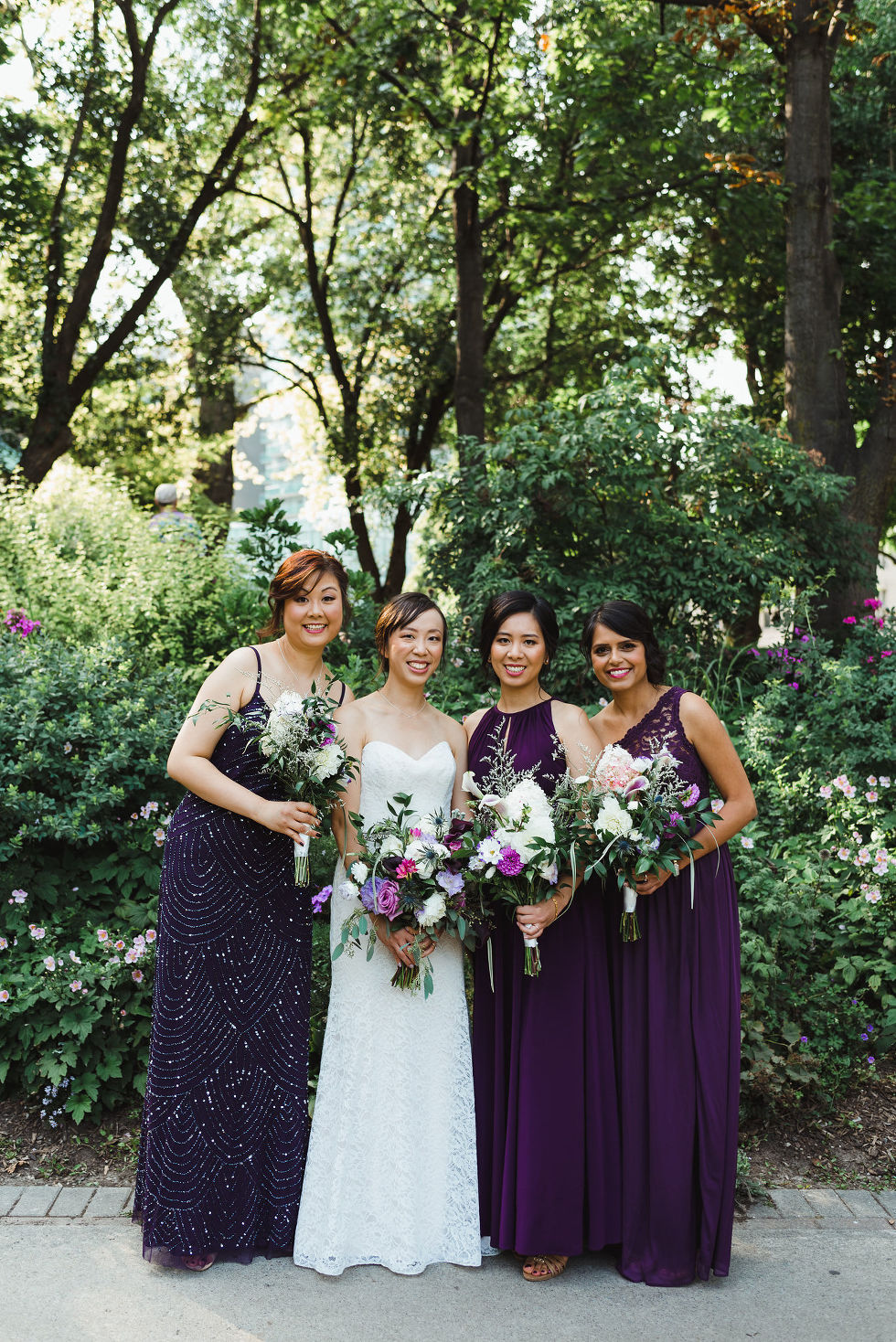 bride standing in the park with her 3 bridesmaids in purple dresses before her Parisian inspired wedding at La Maquette in Toronto Ontario