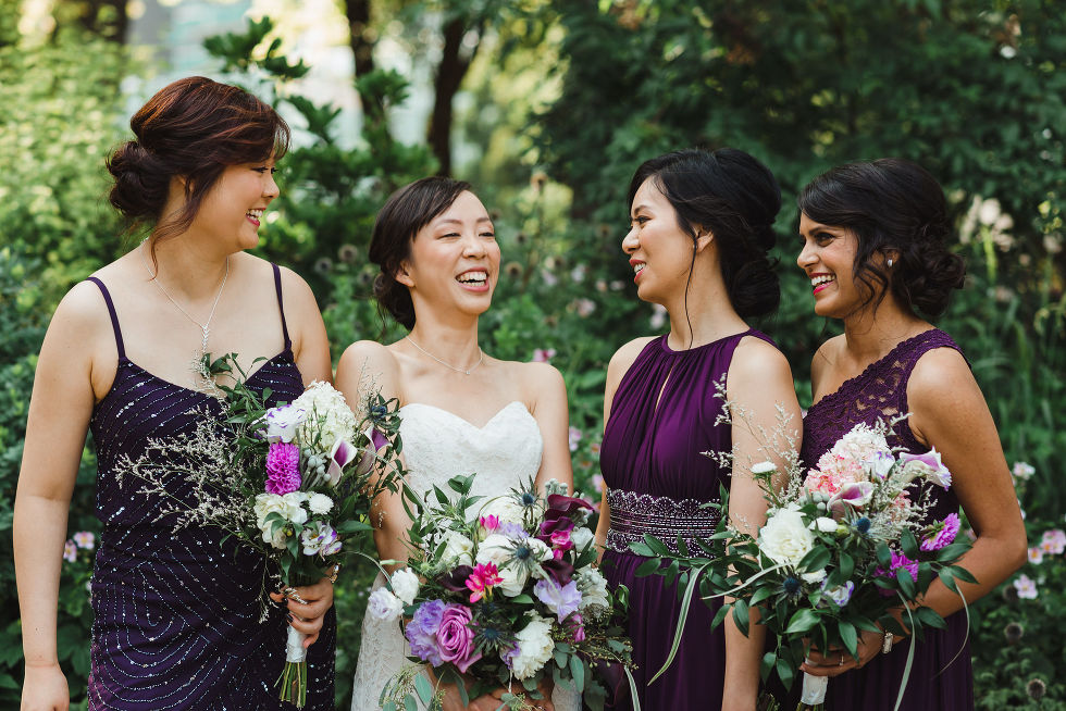 bride laughing in the park with her 3 bridesmaids in purple dresses before her Parisian inspired wedding at La Maquette in Toronto Ontario