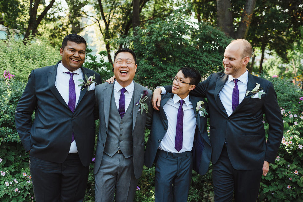 groom laughing with his 3 groomsmen in the park before his Parisian inspired wedding at La Maquette in Toronto Ontario