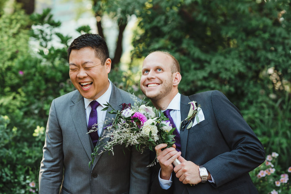 groom laughing as his groomsman leans into him holding a floral bouquet before his Parisian inspired wedding at La Maquette in Toronto Ontario