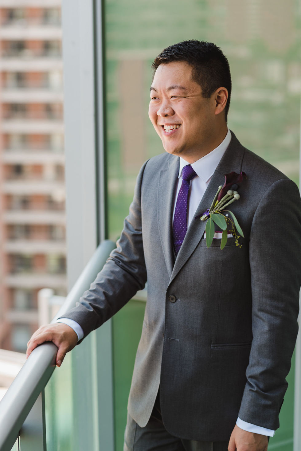 Groom laughing on a condo balcony before his Parisian inspired wedding at La Maquette in Toronto Ontario
