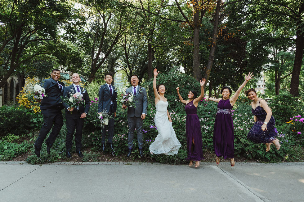 bride and groom jumping in the air in between their wedding party in the park before their Parisian inspired wedding at La Maquette in Toronto Ontario
