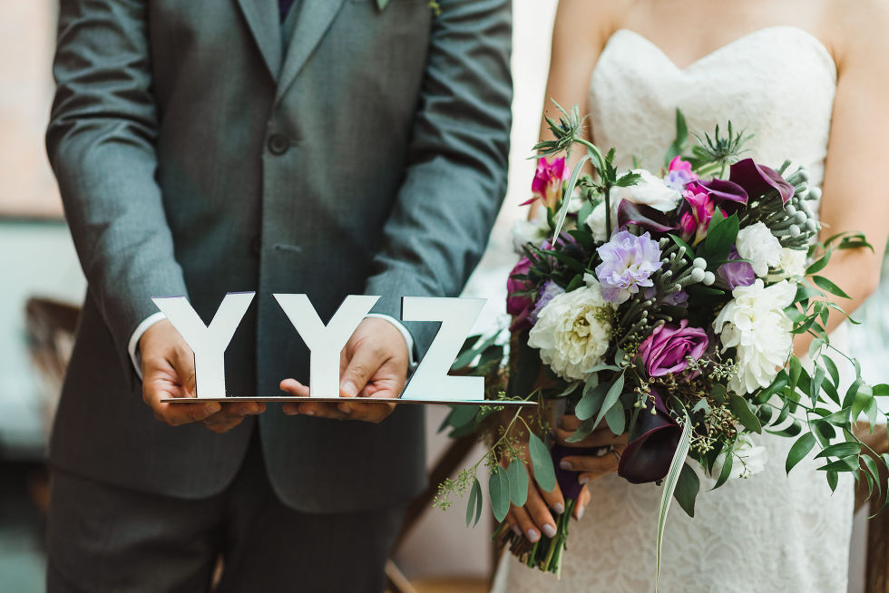 """bride holding floral bouquet standing next to groom holding """"YYZ"""" sign before their Parisian inspired wedding at La Maquette in Toronto Ontario"""