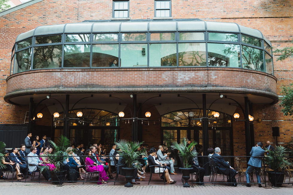 wedding guests seated at the patio of the Parisian inspired La Maquette in Toronto Ontario