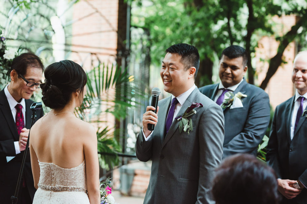 groom reading his vows to the bride with a microphone during their Parisian inspired wedding at La Maquette in Toronto Ontario