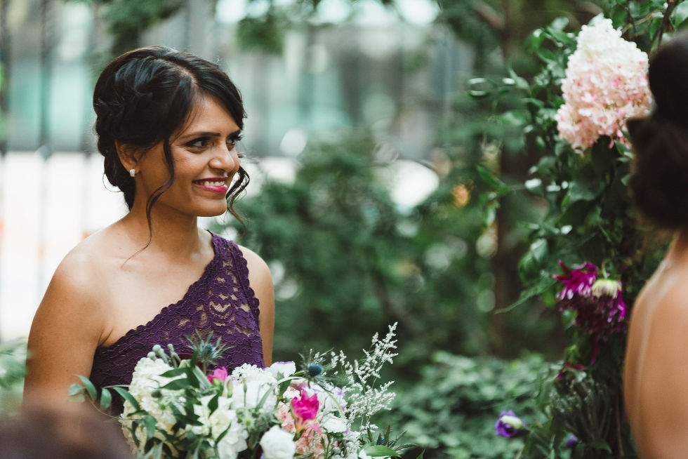 bridesmaid smiling as she watches Parisian inspired wedding ceremony at La Maquette in Toronto Ontario