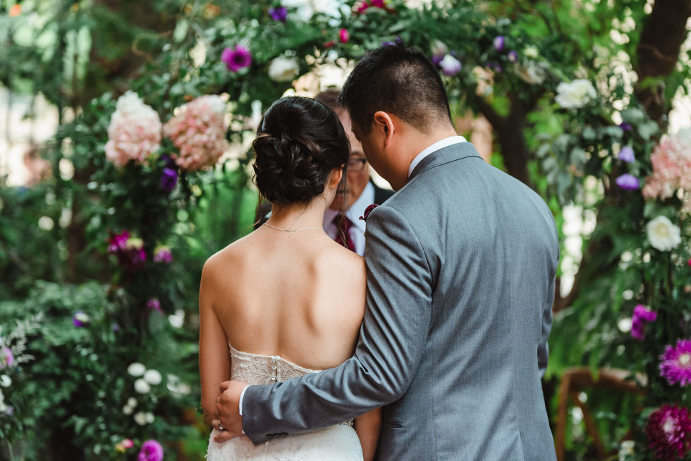 groom with his arm around his bride during their Parisian inspired wedding ceremony in Toronto Ontario at La Maquette