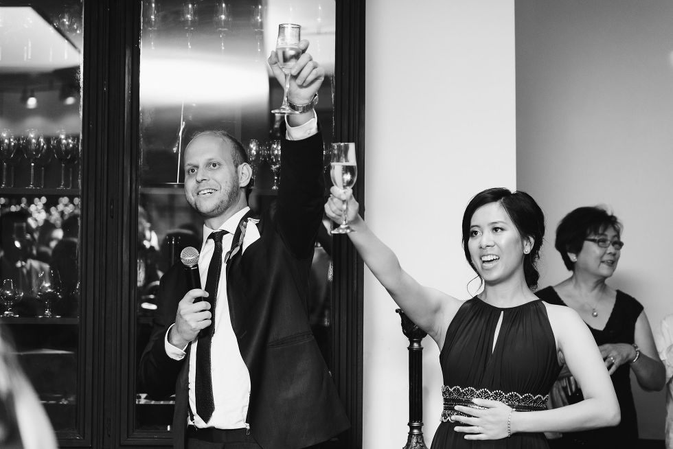 A bridesmaid and a groomsman holding up glasses for a toast after their wedding speech during a Parisian inspired wedding at La Maquette in Toronto Ontario