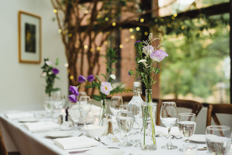white table set with glass vases filled with purple flowers during Parisian inspired wedding at La Maquette in Toronto Ontario