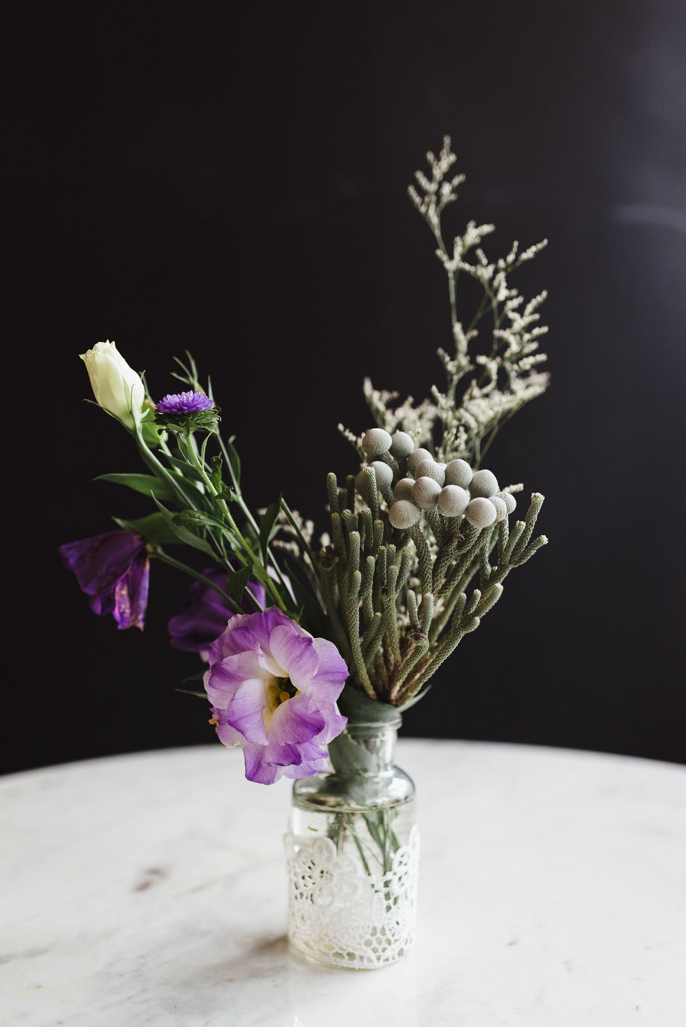 glass vase filled with purple flowers and greenery on top of white marble table during Parisian inspired wedding at La Marquette in Toronto Ontario