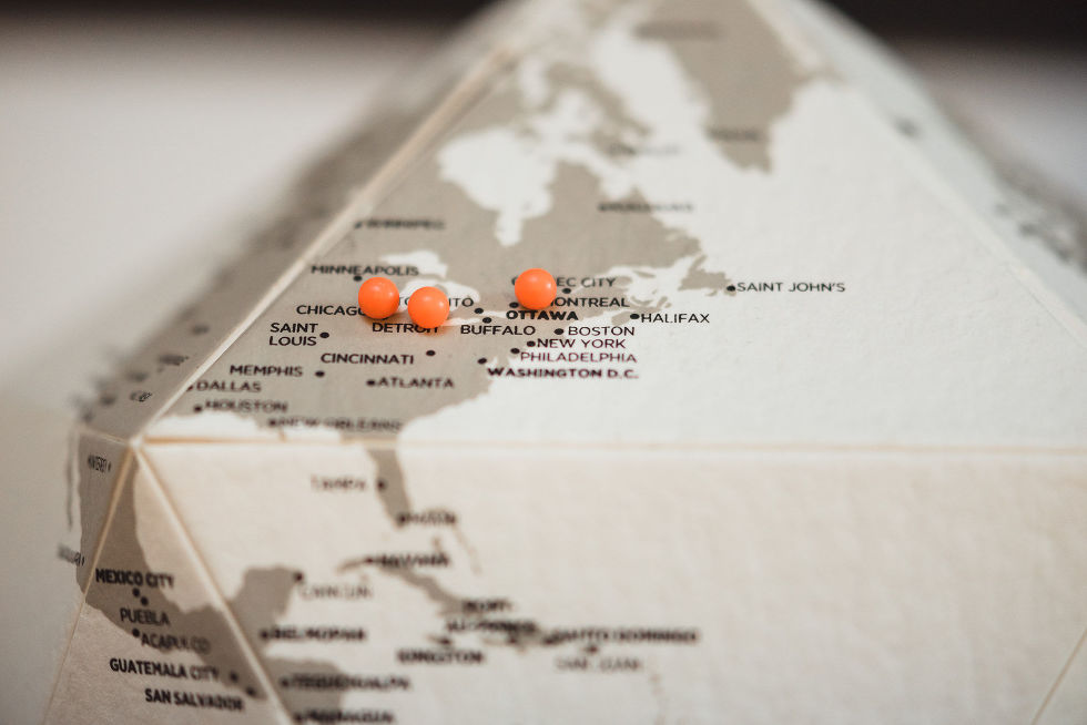 A wedding decoration of a map of Eastern North America with 3 orange pins stuck in different cities during Parisian inspired wedding at La Maquette in Toronto Ontario
