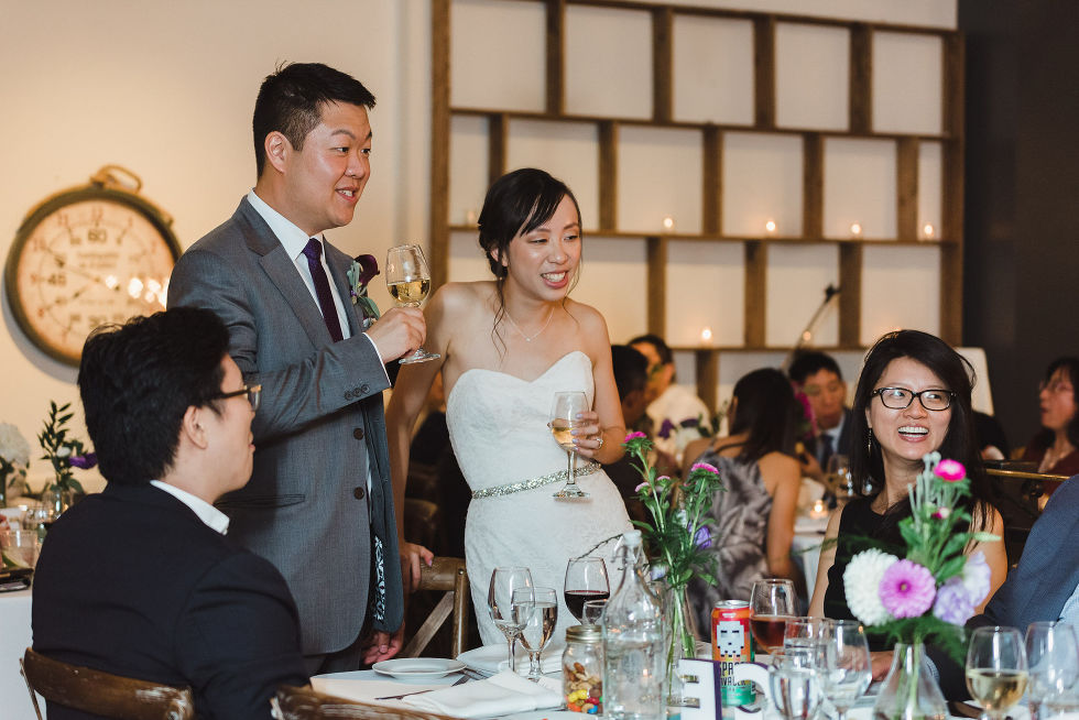 bride and groom standing next to guests seated at a table during their Parisian inspired wedding at La Maquette in Toronto Ontario