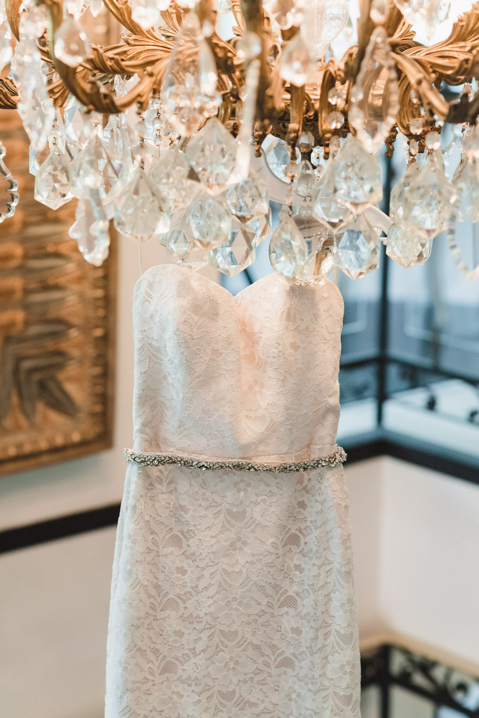 brides white wedding dress hanging from gold and crystal chandelier before Parisian inspired wedding at La Maquette in Toronto Ontario