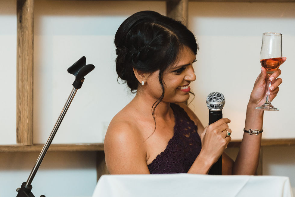 bridesmaid reading her speech into a microphone and toasting the bride and groom with a glass of wine during their Parisian inspired wedding at La Maquette in Toronto Ontario