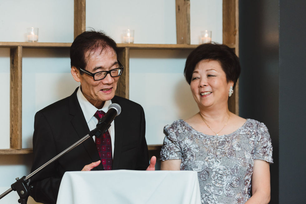mother and father of the groom giving a wedding speech into a microphone during their sons Parisian inspired wedding at La Maquette in Toronto Ontario