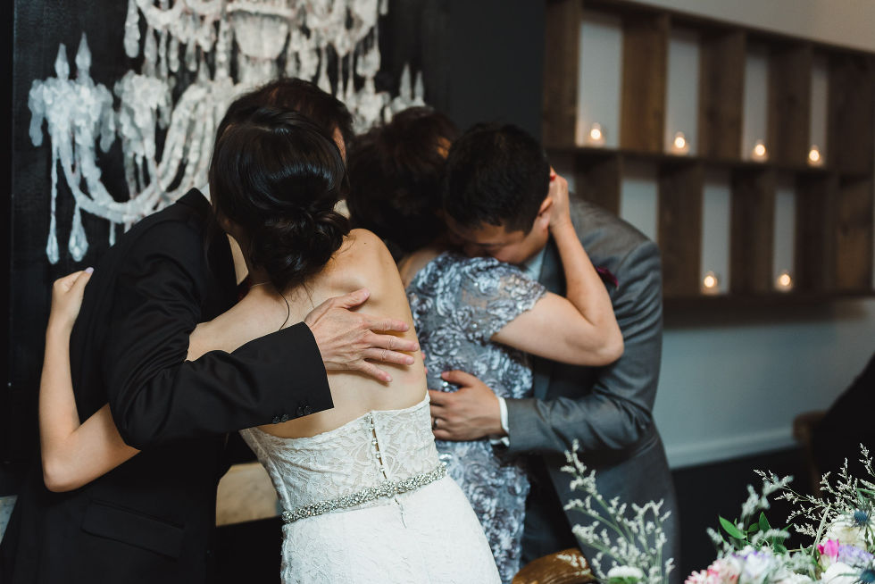 bride and groom hugging the grooms parents during their Parisian inspired wedding at La Maquette in Toronto Ontario
