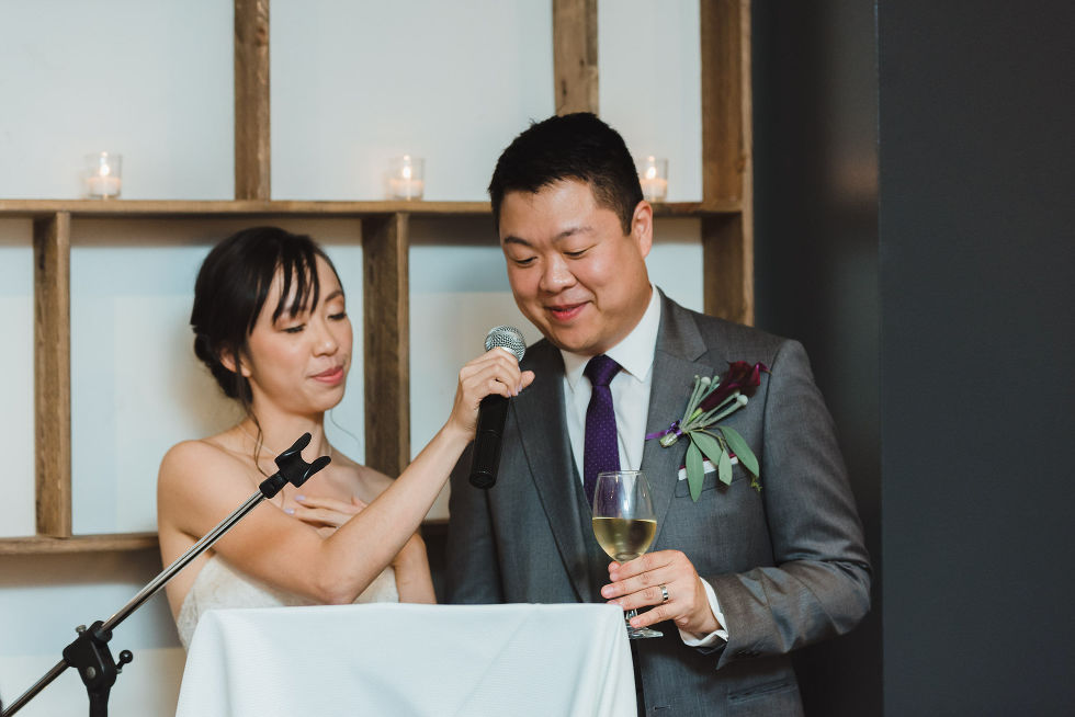 bride holding microphone for groom as he delivers speech and holds a glass of wine during their Parisian inspired wedding at La Maquette in Toronto Ontario