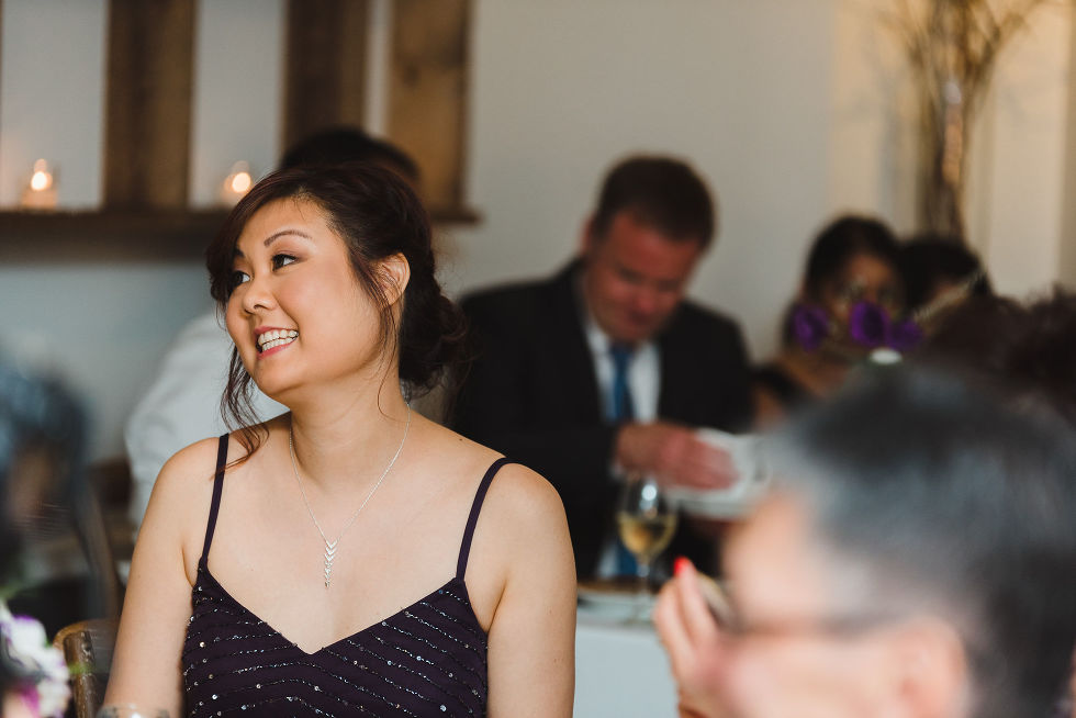 wedding guest smiling as she listens to speeches during Parisian inspired wedding at La Maquette in Toronto Ontario