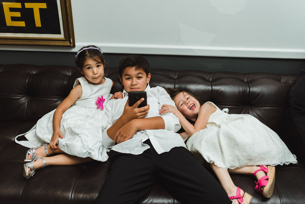 3 young kids sitting on a couch together during a Parisian inspired wedding at La Maquette in Toronto Ontario