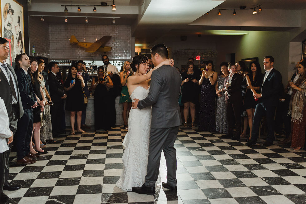 bride and groom slow dance on a black and white checkered floor surrounded by wedding guests during their Parisian inspired wedding at La Maquette in Toronto Ontario
