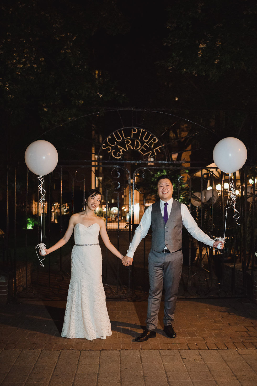 """bride and groom holding hands and white balloons with their other hands in front of a gate that reads """"sculpture garden"""" after their Parisian inspired wedding at La Maquette in Toronto Ontario"""