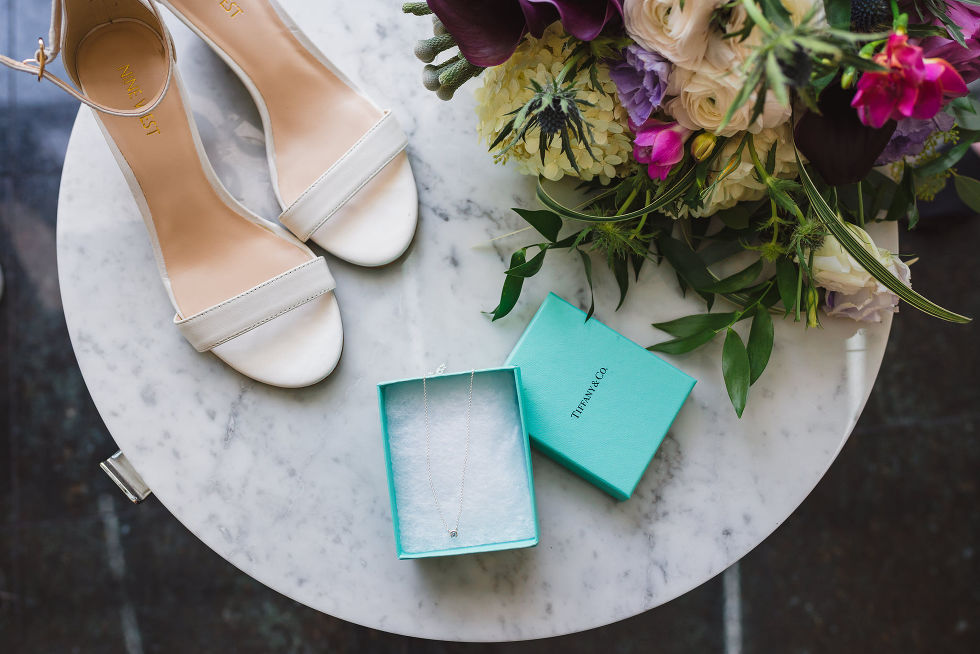 brides white wedding shoes, tiffany necklace in a blue box, and floral bouquet rest on a white marble table before Parisian inspired wedding at La Maquette in Toronto Ontario