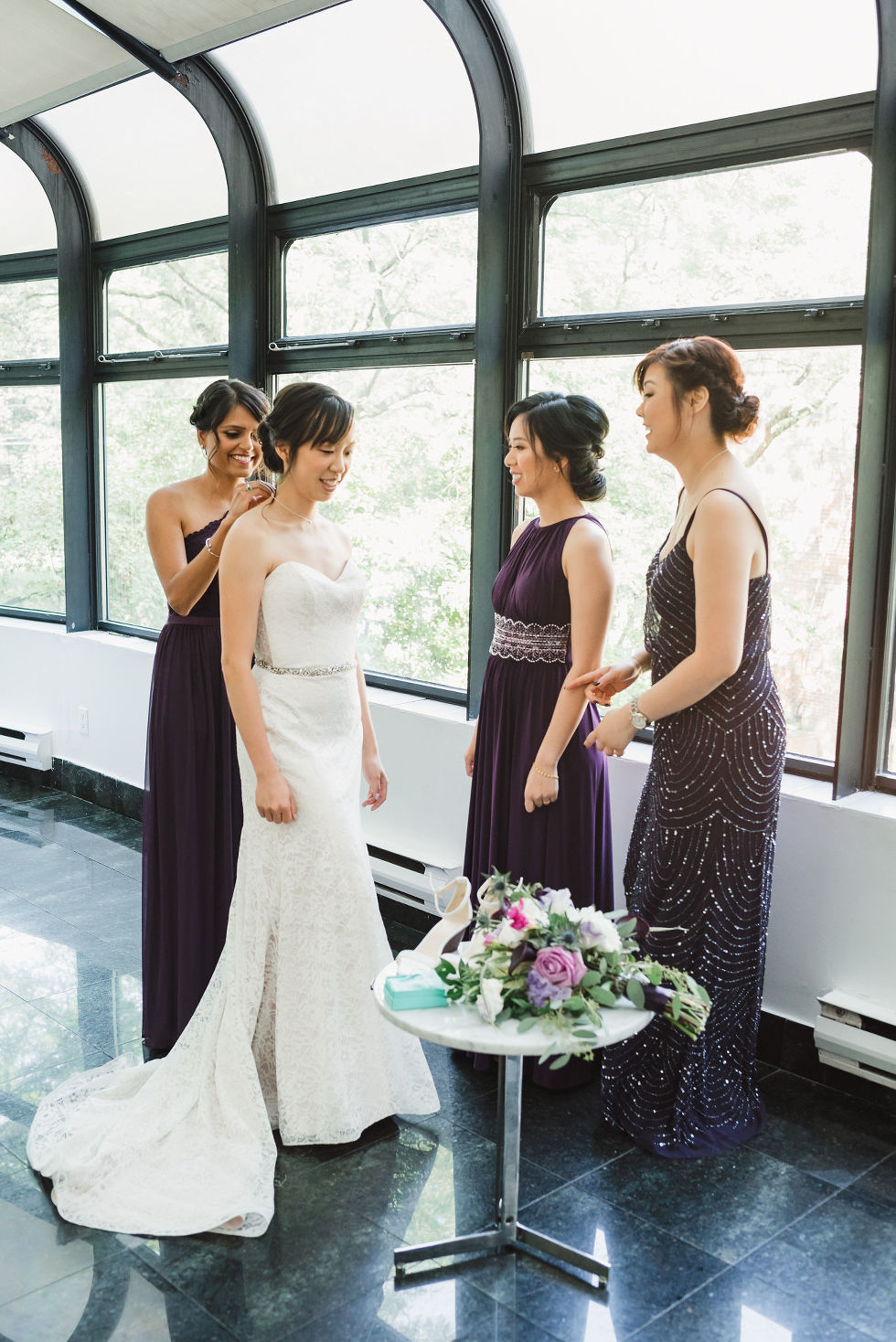 bride in her wedding dress stands in front of 2 bridesmaids as the third bridesmaid helps put on brides necklace behind her before her Parisian inspired wedding at La Maquette in Toronto Ontario