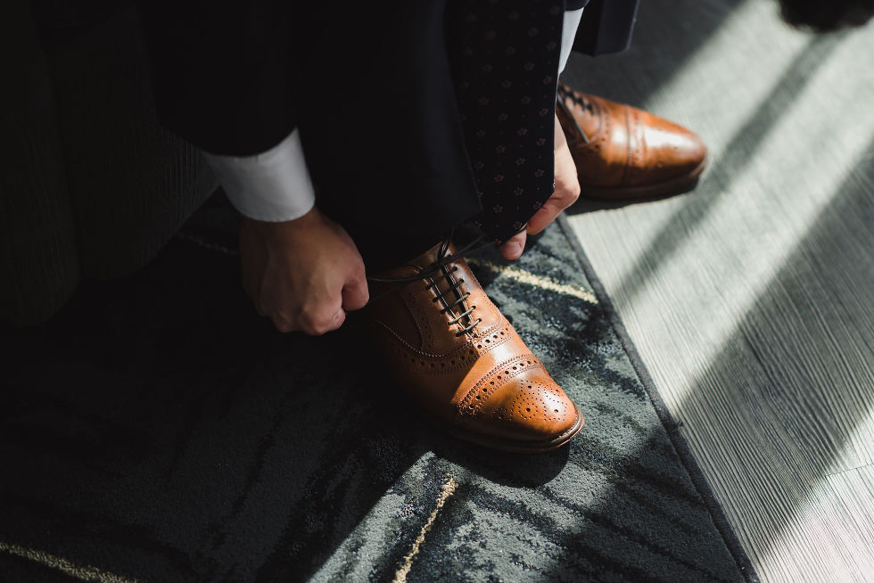 light pouring in on a grooms brown dress shoes as he prepares for his wedding at Fantasy Farms in Toronto Ontario