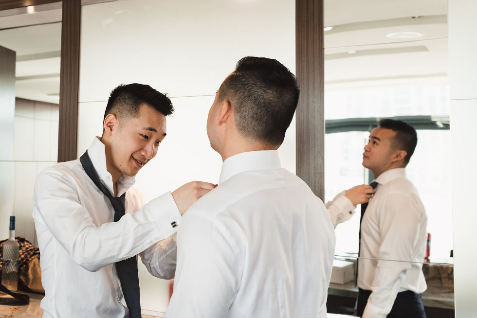 best man helping the groom put on his tie before his wedding at Fantasy Farms in Toronto Ontario