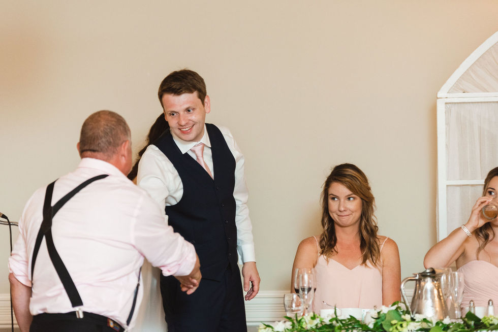 groom standing up from the head table to shake the father of the bride