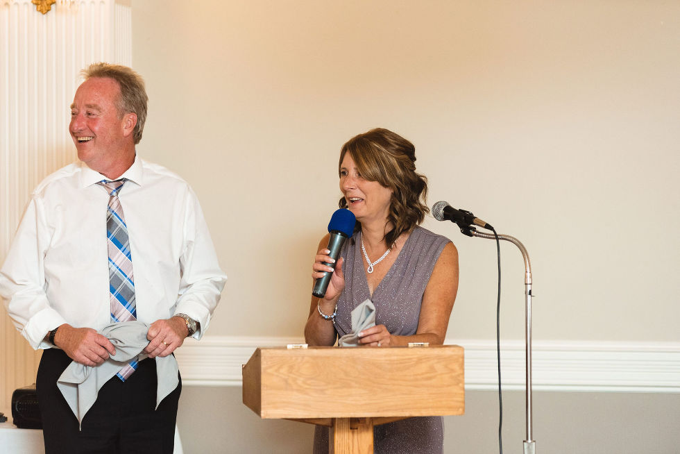mother and father of the bride smiling as they read their speech into the microphone during their daughters special wedding reception at the Royal Ashburn in Pickering
