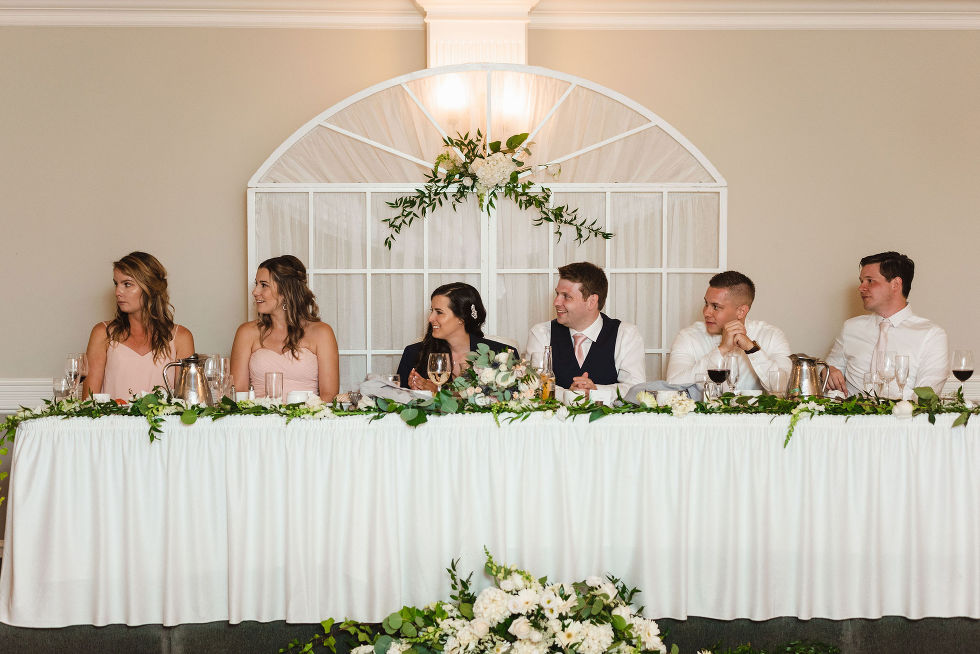 bride and groom sit between their wedding party at the head table during their special wedding reception at the Royal Ashburn in Toronto