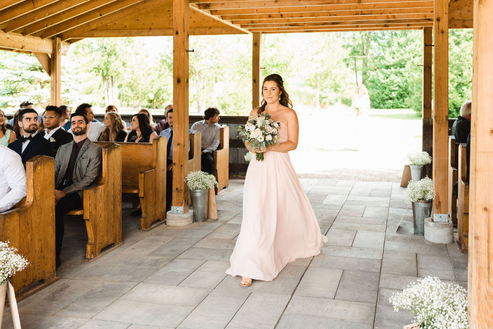 bridesmaid walking down the aisle as wedding guests watch from their seats under wooden beam roof at Carver cottage in Toronto