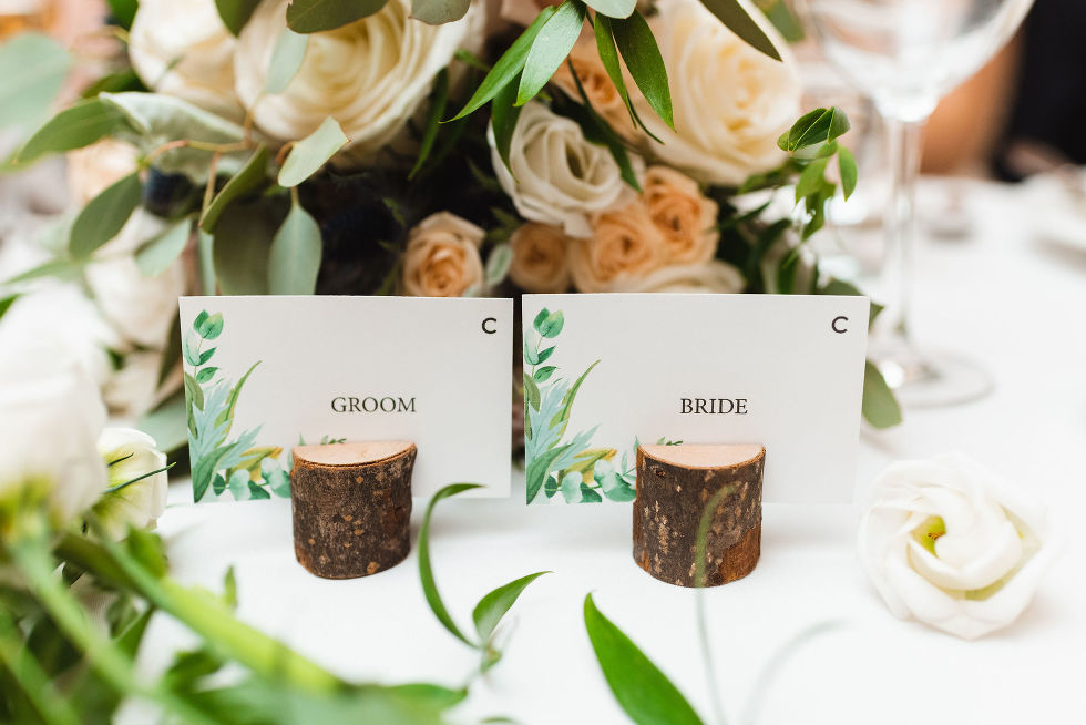 "small wood pieces with slits cut into the centre and name cards placed in them saying ""bride"" and ""groom"" placed on the table during special wedding reception at the Royal Ashburn in Pickering"
