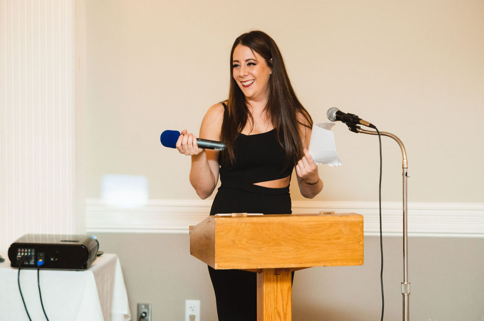 wedding guest smiling as she reads a speech into the microphone during a special wedding reception at the Royal Ashburn in Toronto