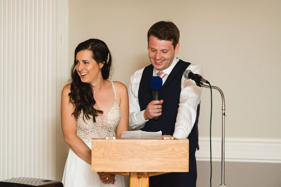 bride and groom laughing as they read their speech into the microphone during their special wedding reception at the Royal Ashburn in Toronto