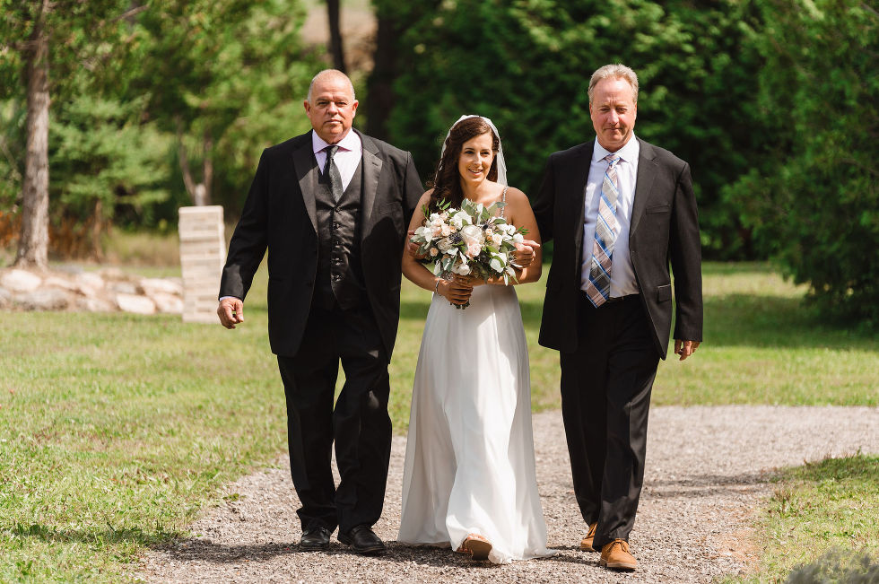 bride being escorted down the aisle by two men in black suits during wedding at Carver cottage in Toronto