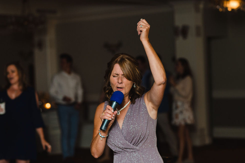 mother of the bride singing into a microphone during her daughters special wedding at the Royal Ashburn in Pickering