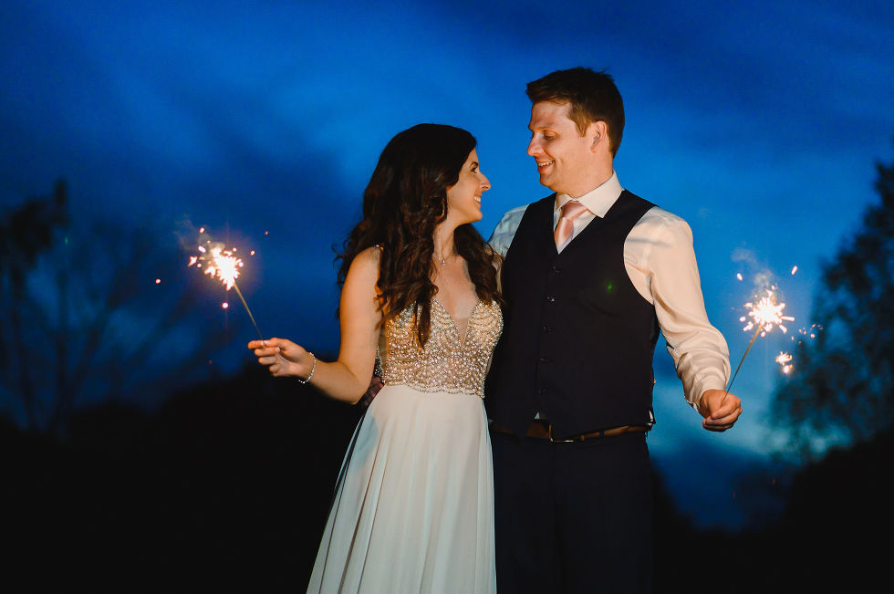 bride and groom standing with arms wrapped around each other and holding sparklers after their special wedding at the Royal Ashburn in Toronto