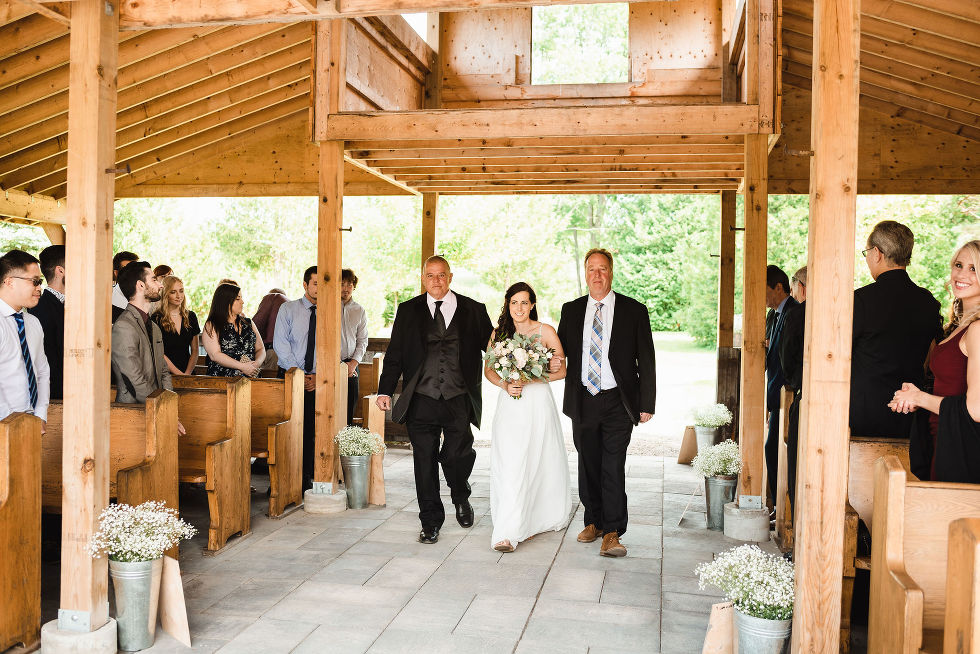 bride being escorted to the alter by two men in black suits for her wedding ceremony at Carvers cottage in Toronto