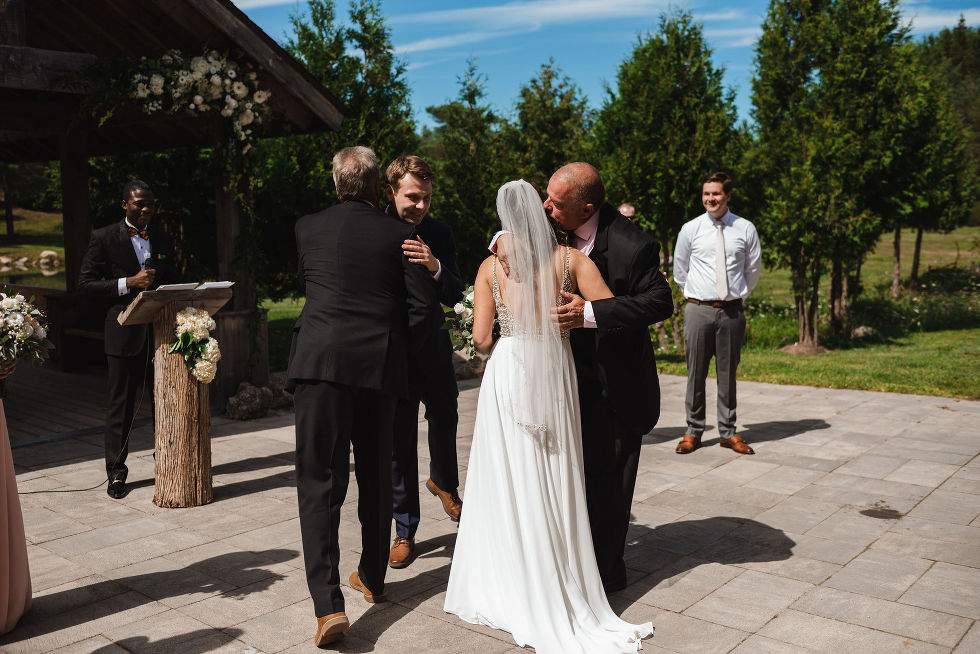 bride and groom hugging their fathers before the wedding ceremony begins at Carvers cottage in Pickering