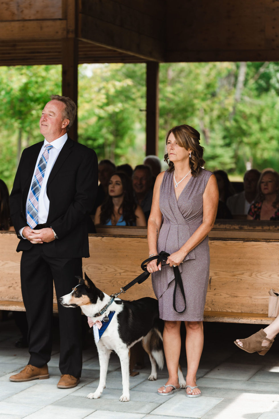 mother of the bride holding their dog on a leash in front of the wedding guests as they watch the couple get married at Carvers cottage in Pickering