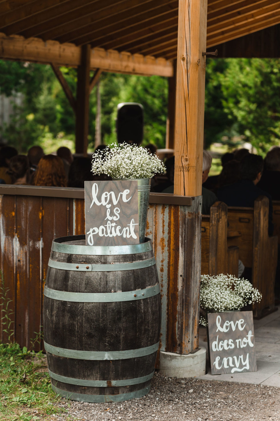 "wooden barrel with white flowers and a sign reading ""love is patient"" on top outside the wedding ceremony barn at Carvers cottage in Pickering"