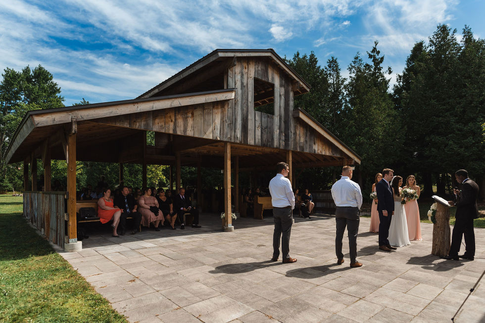 bride and groom getting married on stone patio in front of open style barn at Carvers cottage in Toronto