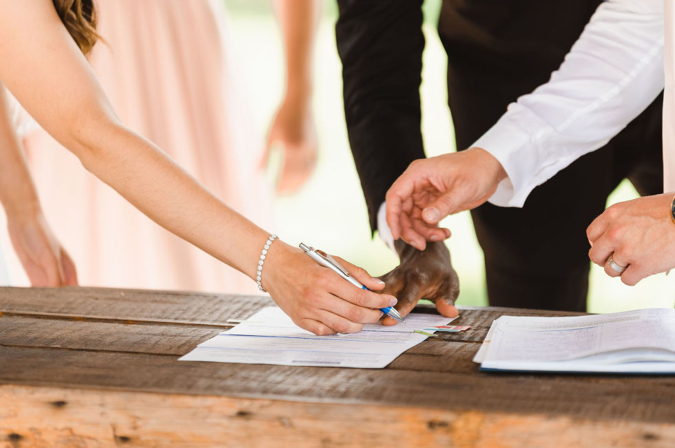 bride and groom being shown where to sign the marriage license on a wood table at Carvers cottage in Toronto